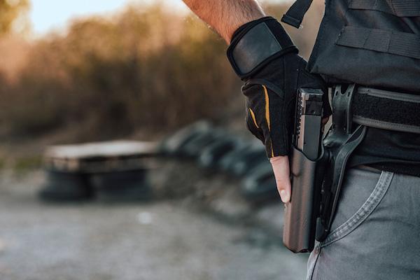 Nahaufnahme eines Mannes, der eine Waffe im Gürtelholster hält